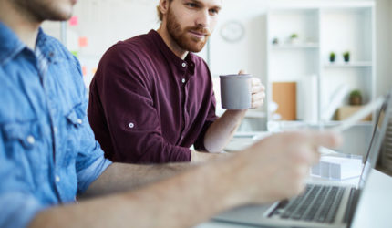 SEO specialist sat with client holding a cup of coffee checking client's website